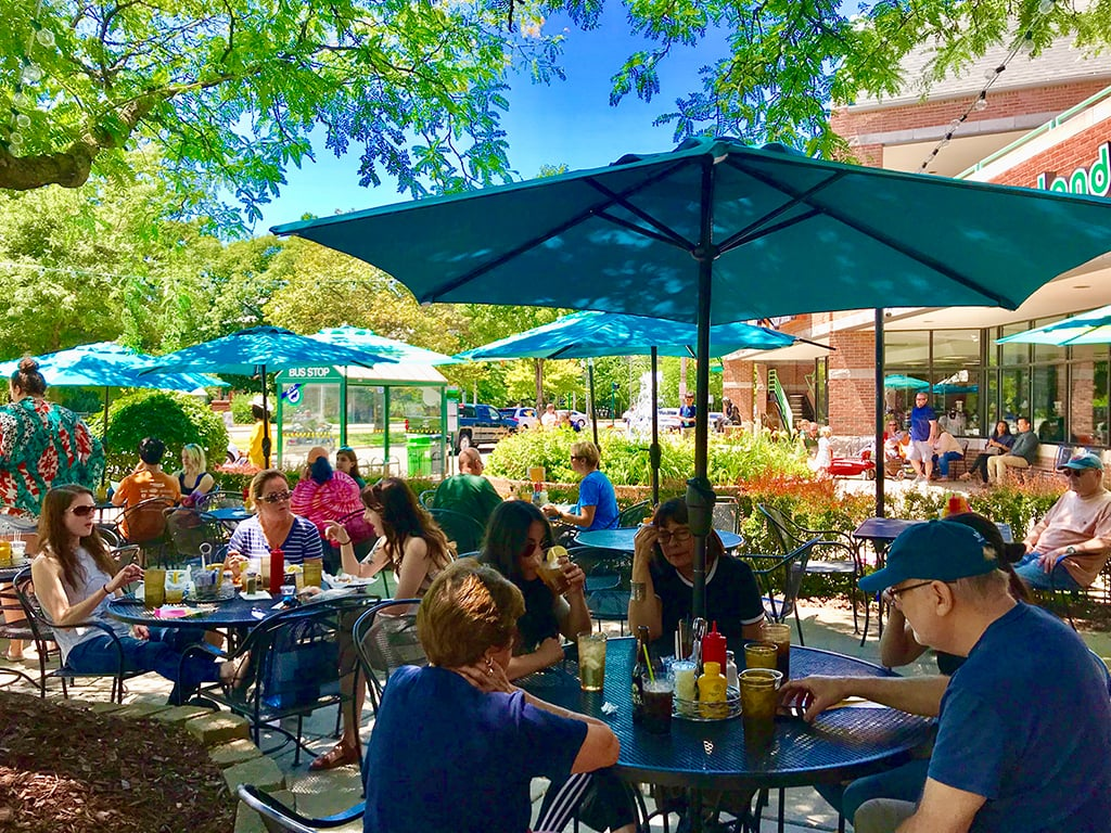 People sitting under the shade of Peanut Barrel's patio umbrellas