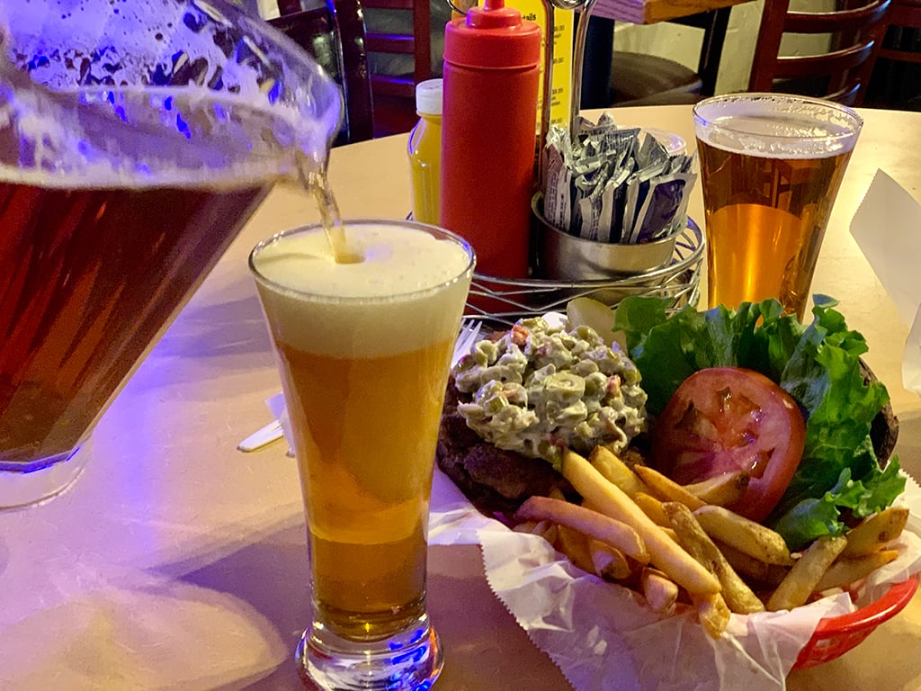 Olive burger and fries with a couple glasses of beer