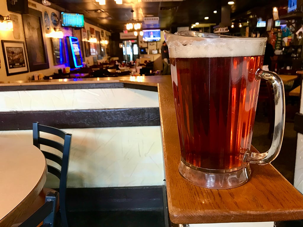 A pitcher of beer sitting on a table